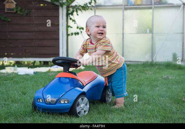 Baby boy with his toy car and crying in lawn, Munich, Bavaria, Germany - Stock Image