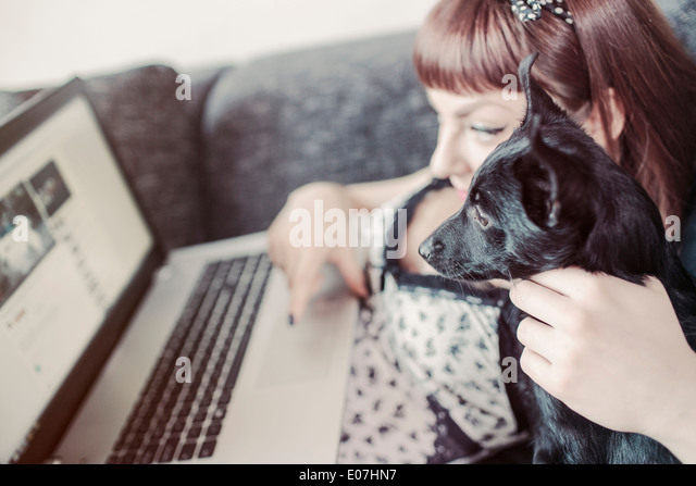 Young woman using laptop alongside her pet dog - Stock Image