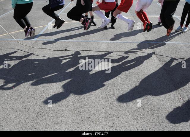 Pupils skipping during playtime at Red Hall Junior School in Darlington, County Durham, UK. - Stock-Bilder