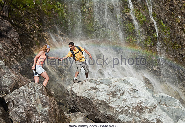 Couple on rocks by waterfall - Stock Image
