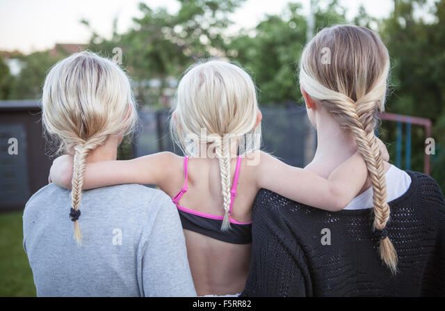 Sweden, Vastergotland, Lerum, Rear view of girls (8-9, 16-17) with braided ponytail standing in backyard - Stock Image