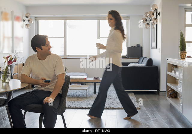 Couple at Home Man using smartphone Woman walking past - Stock-Bilder