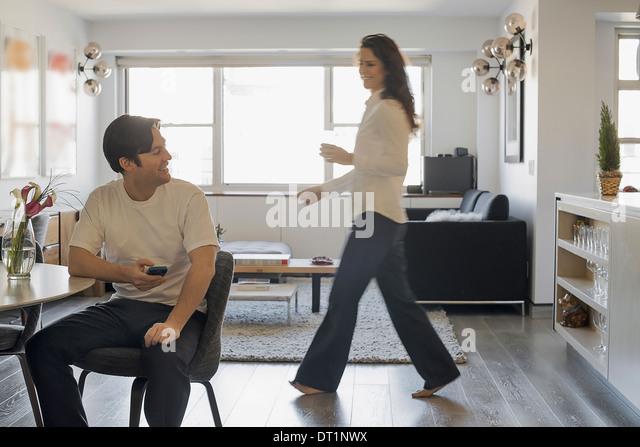 Couple at Home Man using smartphone Woman walking past - Stock-Bilder