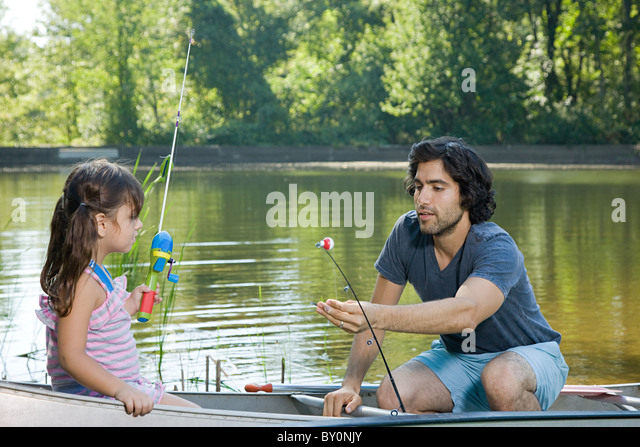 Father and daughter on rowboat with fishing rods - Stock Image