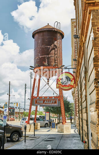 An old rooftop water tank, at street level, stands at the entrance to 'The Alley' in the entertainment district - Stock Image