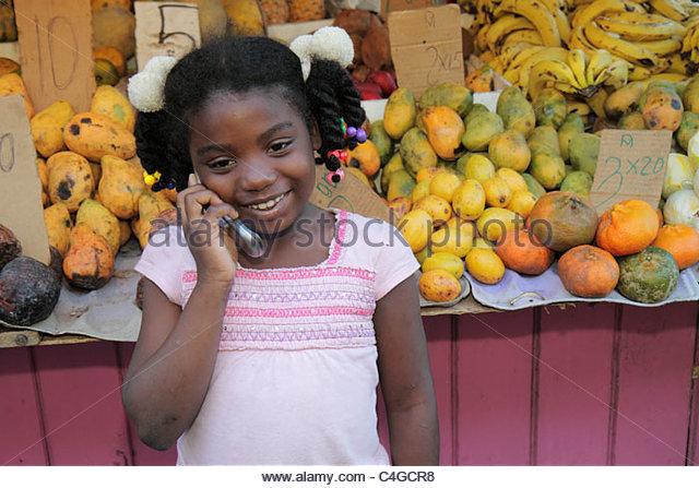 Santo Domingo Dominican Republic Ciudad Colonia Calle Palo Hincado fruit produce stand Hispanic Black girl talking - Stock Image