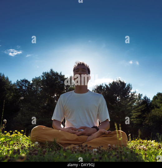 Chinese man meditating outdoors during sunrise in the nature, sitting with crossed legs on grass under blue sky - Stock Image