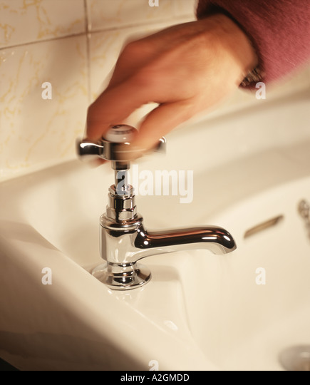 Womans hand turns off the water flowing from a chrome bathroom tap