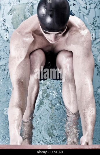Backstroke swimmer in indoor pool in starting position - Stock Image