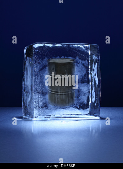 A black oil barrel frozen in a clear block of ice - Stock-Bilder