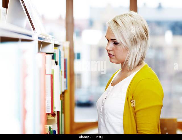 Blond woman in library - Stock Image
