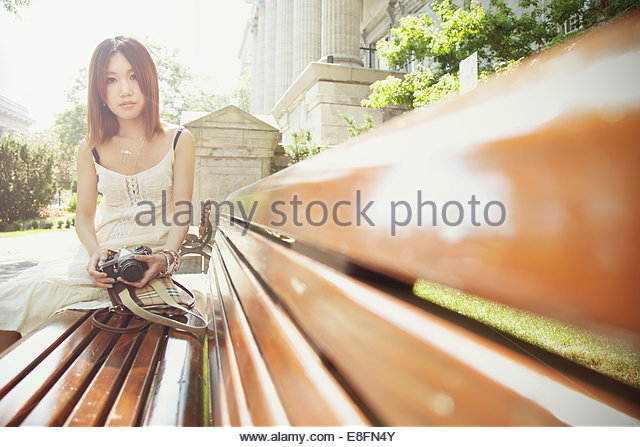 Young woman with camera sitting on bench, Ville-Marie, Quebec, Canada - Stock Image