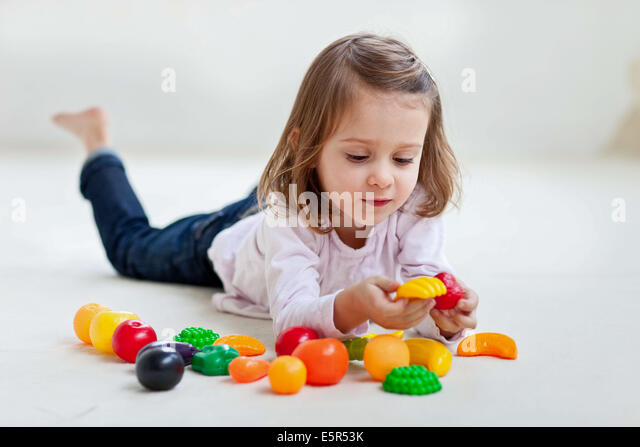 4-year-old girl playing with plastic fruits and vegetables. - Stock Image
