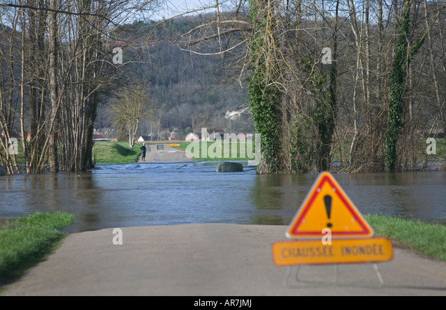 River Dordogne overflows its banks following severe rainfall and takes up a new course, blocking a road in the process. - Stock Image