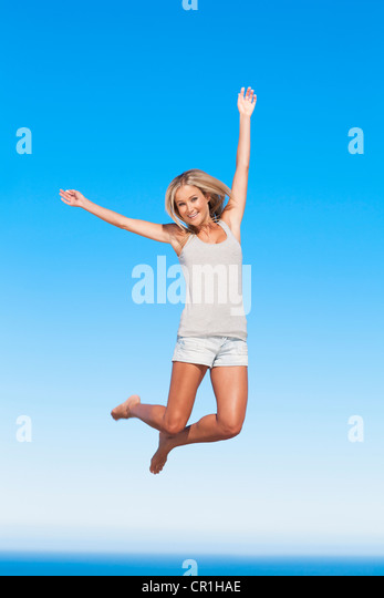 Woman jumping for joy outdoors - Stock Image