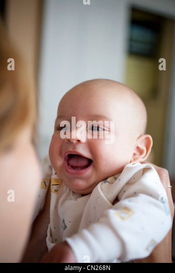 Happy baby held by mother - Stock Image