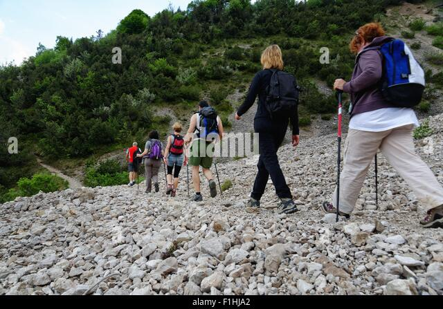 Row of six male and female mature hikers hiking in stoney valley - Stock Image
