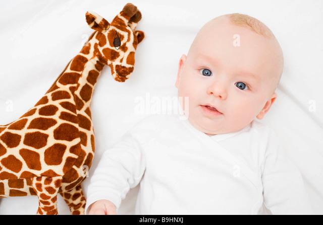Baby laying next to a plush giraffe - Stock Image