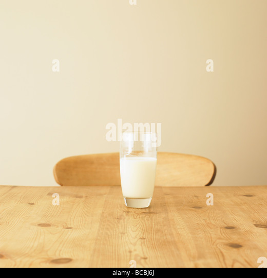 Glass of milk on rustic kitchen table. - Stock Image