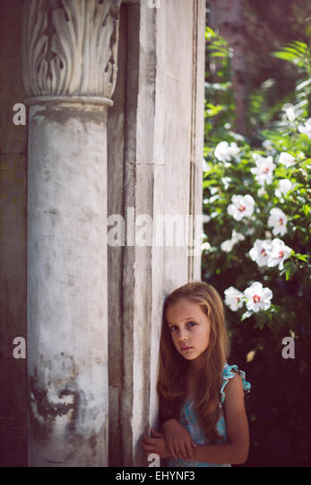 Sad girl standing by a column in the garden - Stock Image