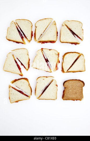 Peanut butter and jelly sandwiches, one on whole wheat bread - Stock Image