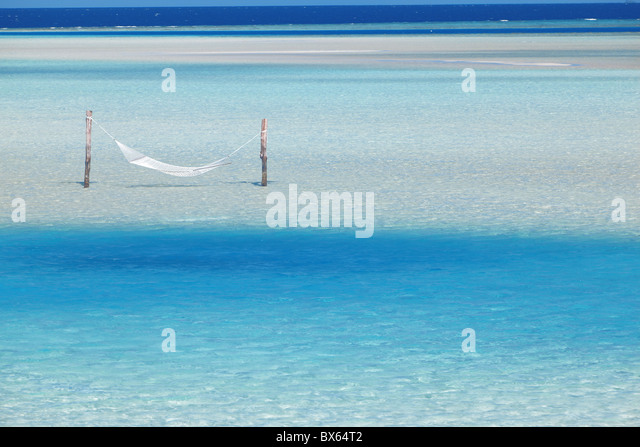 Hammock hanging in shallow clear water, Maldives, Indian Ocean, Asia - Stock Image
