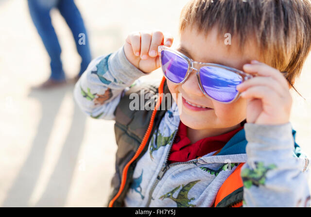 Portrait of smiling little boy putting on coloured sunglasses - Stock Image