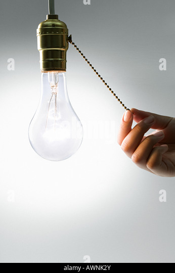 A person pulling a cord on a lightbulb - Stock Image