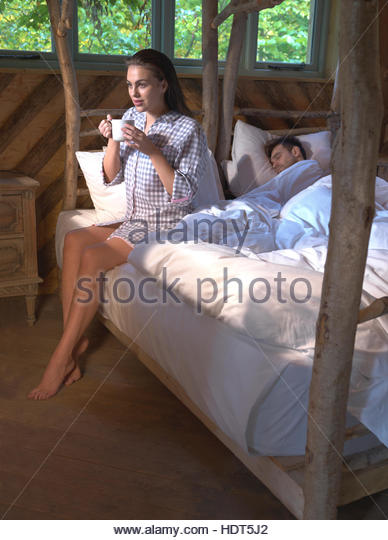 Young woman drinking coffee while her boyfriend is sleeping. - Stock Image