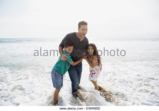 Family wading in ocean surf - Stock Image