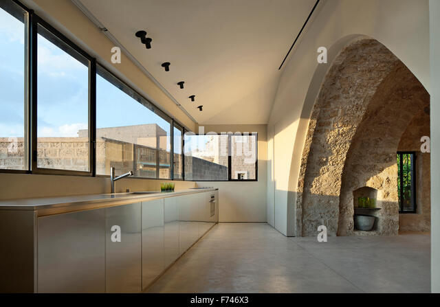 Exposed stone arch and minimalist kitchen with uncurtained windows in  House, Jaffa, Tel Aviv, Israel - Stock Image