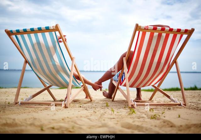 Restful couple sunbathing on the beach - Stock Image