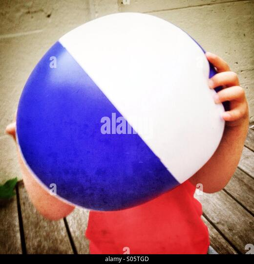 Kid holding beach ball - Stock Image