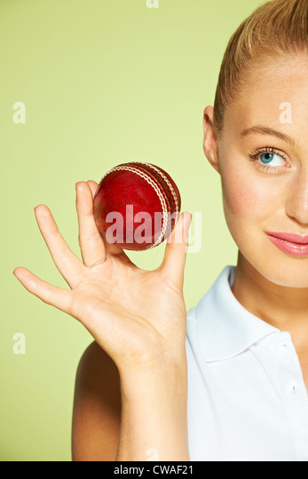 Young woman holding cricket ball - Stock Image