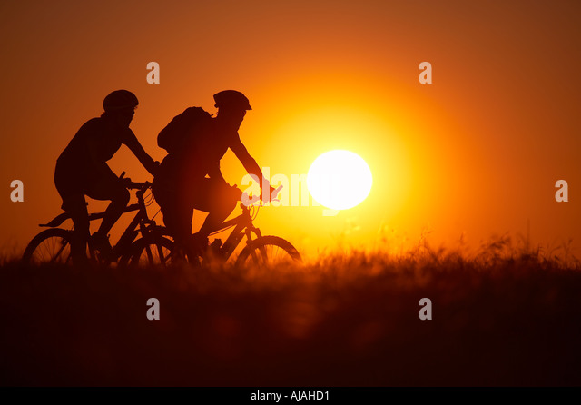 Man woman on mountain bikes cycling on Hambledon Hill above the Blackmore Vale Dorset England UK - Stock Image