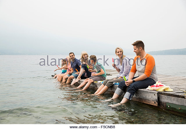 Family eating flavored ice a row lake dock - Stock Image