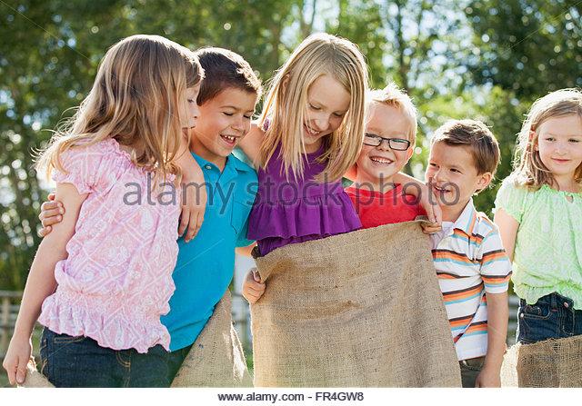 Cousins having fun with potato sacks - Stock Image