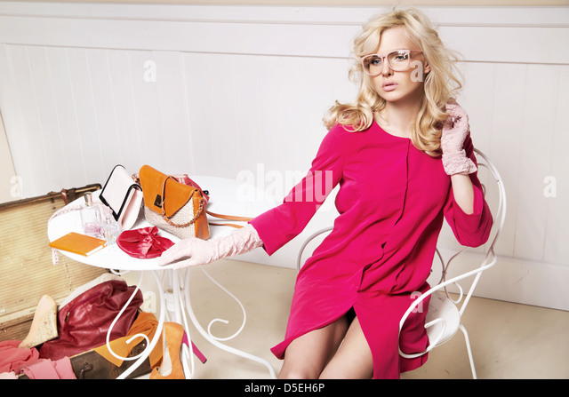 Stylish blonde woman in room full off fashion elements - Stock Image