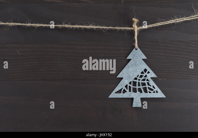 Close Up of Metal Pine Tree Ornament against dark wood background - Stock Image