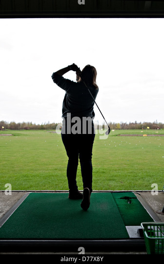 A female hitting a golf ball at a driving range - Stock Image