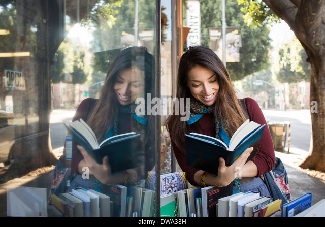 Young woman reading book by shop window - Stock Image