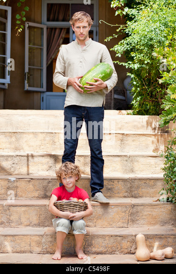 Father and son carrying fruits - Stock Image