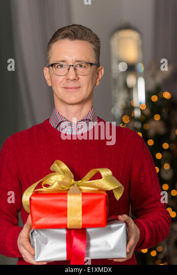 Portrait of mature man holding stack of Christmas presents - Stock Image