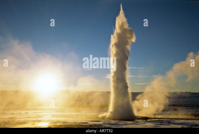 Strokkur geyser, in Haukadalur geothermal area, erupting during winter sunrise in Geysir, Iceland - Stock Image