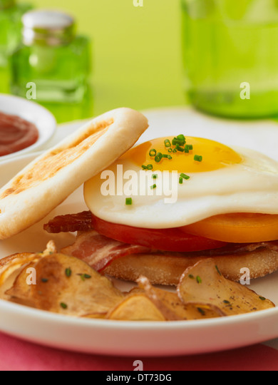 A close up shot of a sunny side up egg sandwich with bacon and tomatoes on an English muffin with breakfast fried - Stock Image