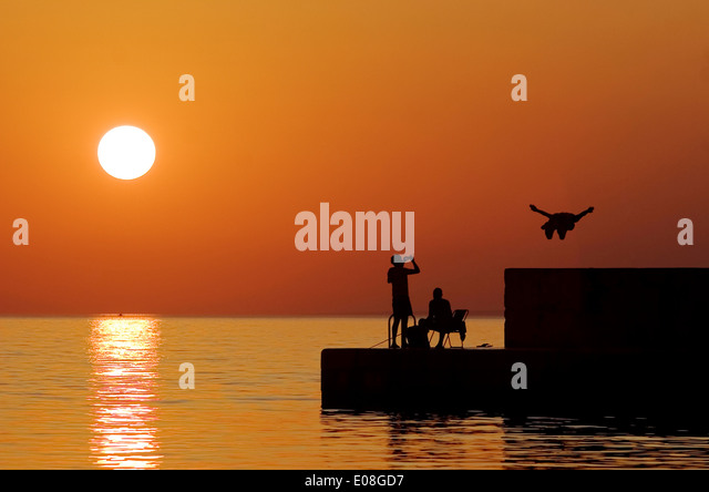 People on the waterfront at sunset, Adriatic Sea, Croatia - Stock Image