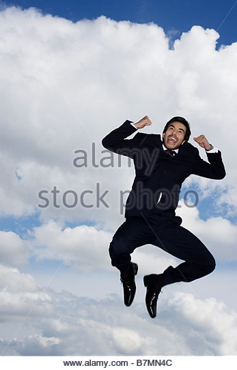 A businessman leaping in the air - Stock Image
