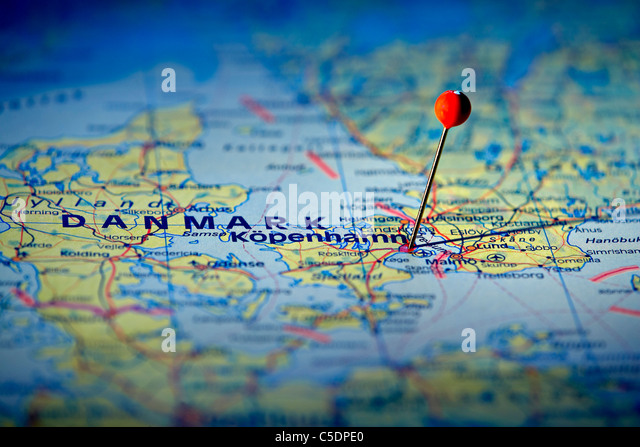 Close-up of a red map pin on Copenhagen at a map - Stock Image