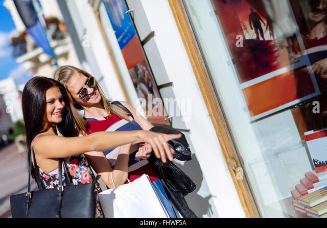 Beautiful women shopping outdoors and looking at store windows - Stock Image