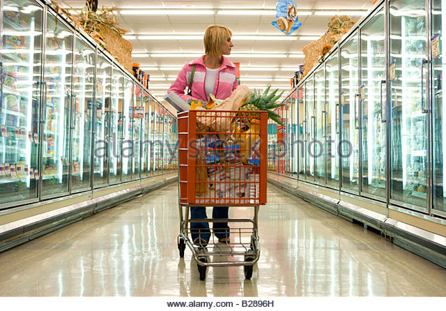 Woman grocery shopping in frozen foods section - Stock Image